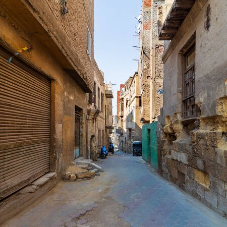 Aged houses with crumbling walls located on narrow abandoned street on sunny day in old Cairo, Egypt Stock Photo - 131870220