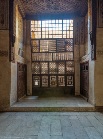 Interleaved wooden window (Mashrabiya), wooden embedded cupboards, and wooden decorated ceiling at ottoman historic Beit El Set Waseela building (Waseela Hanem House), Old Cairo, Egypt Stock Photo - 127467275