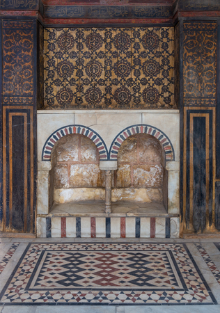 Wooden wall decorated with painted floral patterns, embedded arched niche and marble floor decorated with geometric patterns at ottoman era historic house of Moustafa Gaafar Al Seleehdar, Cairo, Egypt Stock Photo - 127467289