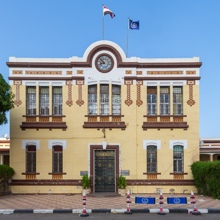 Facade of Financial Affairs Department of Suez Canal Authority with yellow bricks, Single door, windows covered with iron bars, and clock at the top of the building, located in Port Fuad, Cairo, Egypt Stock Photo - 127467293