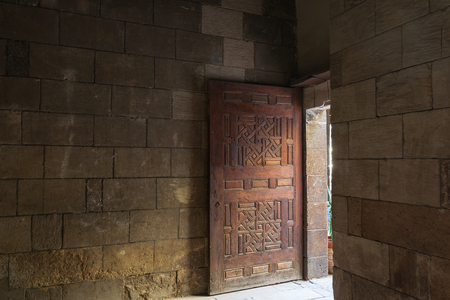 Old abandoned room with stone bricks and grunge weathered wooden decorated door, Old Cairo, Egypt Stock Photo - 127467294