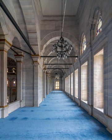 Passage in Nuruosmaniye Mosque, a public Ottoman Baroque style mosque, with columns, arches and floor covered with blue carpet lighted by side windows located in Shemberlitash, Fatih, Istanbul, Turkey Stock Photo - 127467300