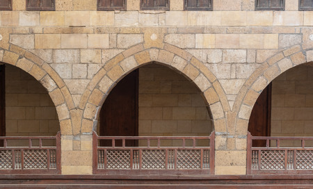 Front view of three arches with interleaved wooden balustrades at the arcade surrounding the courtyard of caravanserai (Wikala) of al-Ghuri, Medieval Cairo, Egypt Stock Photo - 127467301