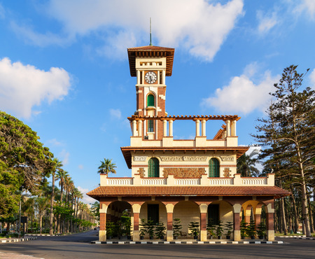 Facade of the clock tower in Montaza public park with decorated stone wall, green wooden window shutters, and red tile canopies after sunrise, Alexandria, Egypt Stock Photo - 127467307