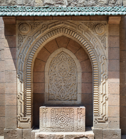 Stone sculpted drinking fountain (Sabil) with engraved floral decorations at the public garden of The Manial Palace of Prince Mohammed Ali Tewfik, Cairo, Egypt Stock Photo - 127467309