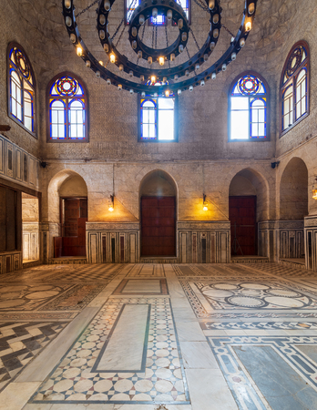 Interior shot of a hall at Mamluk era Sultan al Ghuri Mausoleum with decorated marble floor, stained glass windows, and bricks stone wall, Cairo, Egypt Stock Photo - 127467312