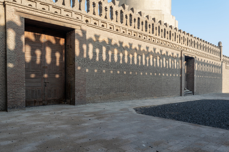 Stone bricks old decorated fence with wooden doors and shadows of decorations of the opposite fence, Mosque of Ibn Tulun, Old Cairo, Egypt Stock Photo - 127467315