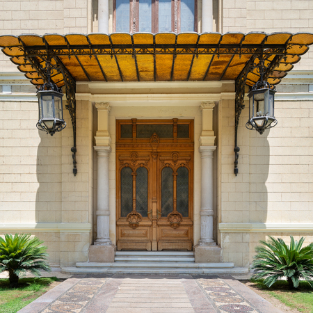 Decorated antique wooden door in a stone bricks wall, sunshade and two lanterns, Facade of Abdeen Palace, Cairo, Egypt Stock Photo - 127467318