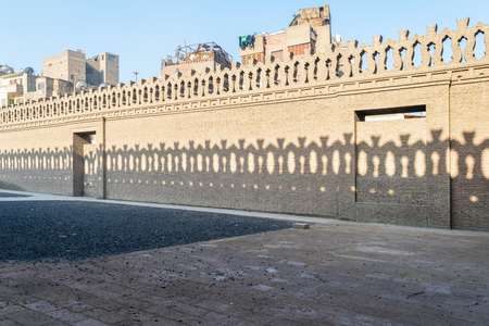 Stone bricks old decorated fence with wooden doors and shadows of decorations of the opposite fence, Mosque of Ibn Tulun, Old Cairo, Egypt Stock Photo - 127467320