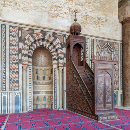Colorful decorated marble wall with engraved niche (Mihrab) and wooden platform (Minbar) at the Mosque of Al Nasir Mohammad Ibn Qalawun, situated in the Citadel of Cairo in Egypt Stock Photo - 127467569