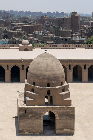 Aerial view of ablution fountain at the courtyard of Ibn Tulun public historical mosque with grunge houses in the background, Old Cairo, Egypt Stock Photo - 127467587