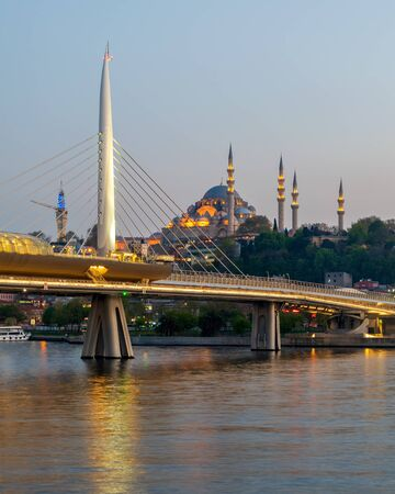 Golden Horn Metro Bridge, Halic Bridge overlapping Suleymaniye Mosque before sunset, Istanbul, Turkey Stock Photo - 131870576