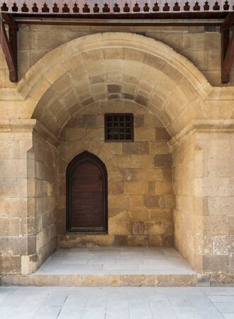 Wooden grunge door and window covered with interleaved wooden grid in recessed stone bricks wall at facade of caravansary - Wikala of Bazaraa, suited in Gamalia district, Medieval Cairo, Egypt Stock Photo - 131870747