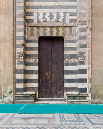 Wooden aged door surrounded by striped black and white marble decorations and stone wall at the courtyard of Sultan Hassan Mosque, Cairo, Egypt Stock Photo - 131870396
