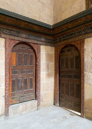 Two wooden aged ornate vaulted perpendicular doors on stone bricks walls, Medieval Cairo, Egypt Stock Photo - 131870799
