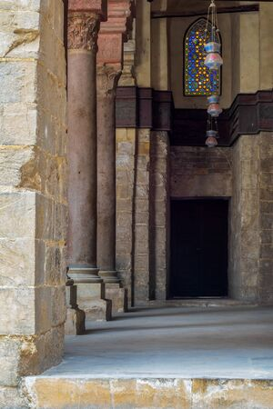 Passage at Sultan Qalawun Mosque with stone columns, colored stained glass windows and wooden door, Cairo, Egypt Stock Photo - 131870614