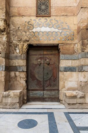 Wooden decorated copper plated door and stone bricks wall leading to Sultan Barquq mosque, Al-Moez Street, Old Cairo, Egypt Stock Photo - 131870312