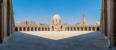 Panorama of the courtyard of Ibn Tulun public historic mosque, Cairo, Egypt, with the ablution fountain and the minaret Stock Photo - 131870275