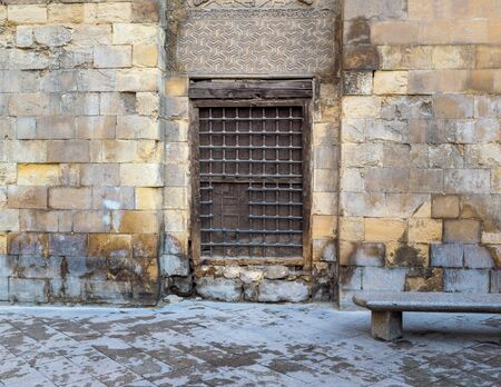 Wooden window with decorated iron grid over stone bricks wall and marble garden bench, Moez Street, Cairo, Egypt Stock Photo - 131870352