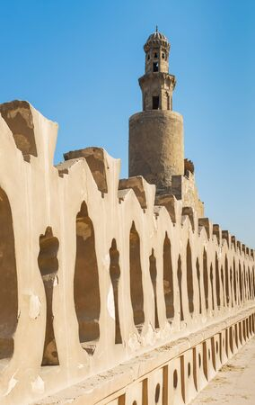 Stone bricks old decorated fence of Mosque of Ibn Tulun revealing minaret of the mosque, Medieval Cairo, Egypt Stock Photo - 131870471