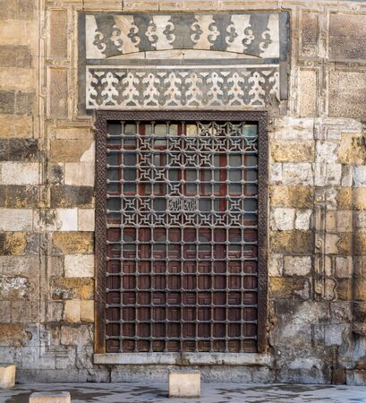 Wooden grunge window with decorated iron grid over stone bricks wall, Moez Street, Cairo, Egypt Stock Photo - 131870326
