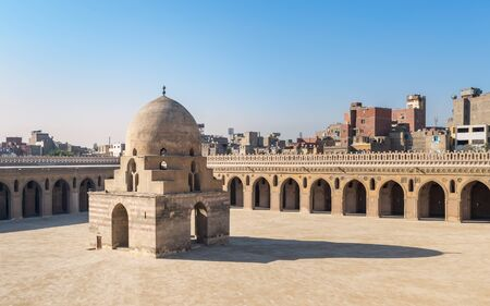 Courtyard of Ibn Tulun public historical mosque with ablution fountain and arched passages surrounding the courtyard in the background, Sayyida Zaynab district, Medieval Cairo, Egypt Stock Photo - 131870832