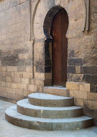 Three steps leading to closed wooden weathered arched door, Ibn Tulun Mosque, Sayyida Zaynab district, Medieval Cairo, Egypt Stock Photo - 131870332