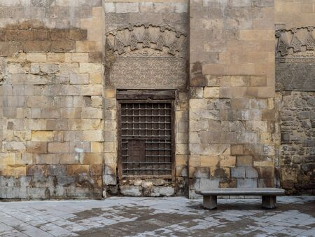 Wooden window with decorated iron grid over stone bricks wall and marble garden bench, Moez Street, Cairo, Egypt Stock Photo - 131870475