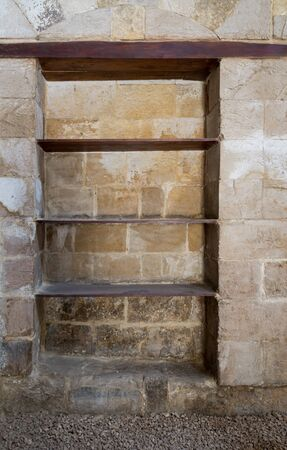 Recessed frame, Niche with wooden shelves in an old weathered stone bricks wall, Medieval Cairo, Egypt Stock Photo - 131870923