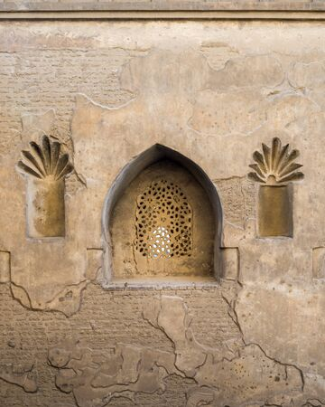 Perforated arched stucco window decorated with floral patterns, one of the traditions of the Mamluk era, Outer wall of Mosque of Ibn Tulun, Sayyida Zaynab district, Medieval Cairo, Egypt Stock Photo - 131870818