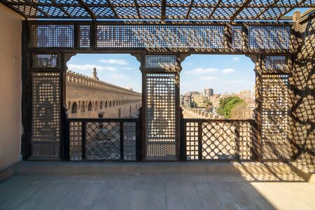 Passage surrounding the Mosque of Ibn Tulun framed by interleaved wooden perforated wall, Mashrabiya, Medieval Cairo, Egypt Stock Photo - 131871003
