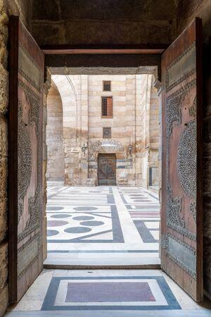 Opened door leading to the courtyard of Al-Sultan Al-Zahir Barquq mosque. Al-Moez Street, Old Cairo, Egypt Stock Photo - 131871058