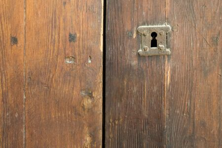 Rusted keyhole over an old weathered wooden grungy door Stock Photo - 131870385