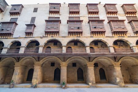 Facade of historic Wikala of Bazaraa building, with vaulted arcades and oriental wooden oriel windows, suited in Tombakshia street, Gamalia district, Medieval Cairo, Egypt Stock Photo - 131870604