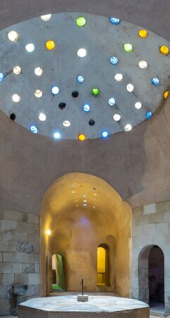 Arched stone wall lighted by colored circular shaped roof holes at a historical traditional Turkish style bath named Hamam Inal, Medieval Cairo, Egypt Banque d'images