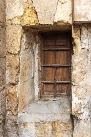 Wooden grunge closed window with wrought iron grid in stone bricks wall, Old Cairo, Egypt Stock Photo - 131871055