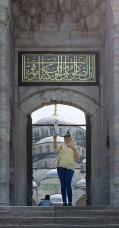 Istanbul, Turkey - April 16 2017: Female tourist taking a selfie photo in front of one of the entrances of the Blue Mosque - Sultan Ahmed Mosque Stock Photo - 133073828