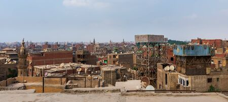 Shabby buildings with satellite dishes on rooftops located against blue sky in ancient city of Cairo, Egypt Stock Photo - 131870540