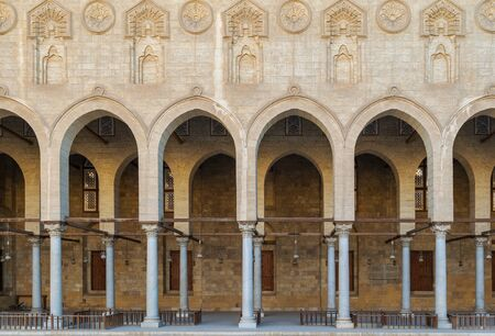 Arched corridor surrounding the courtyard of public ancient mosque of Sultan Al Moaayad, Old Cairo, Egypt Stock Photo