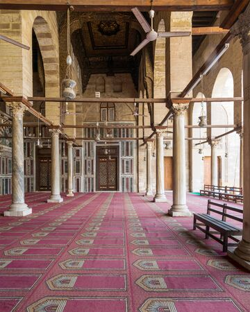 Corridor at public historic mosque of Sultan Al Moaayad, ending with colorful marble wall and wooden door decorated with arabesque ornaments, Old Cairo, Egypt Stock Photo