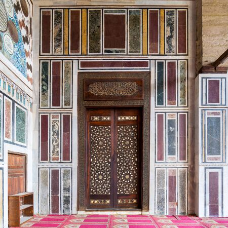 Old colorful marble wall with wooden door decorated with arabesque ornaments in public historic Al Moaayad Mosque, Cairo, Egypt Stock Photo - 131871230