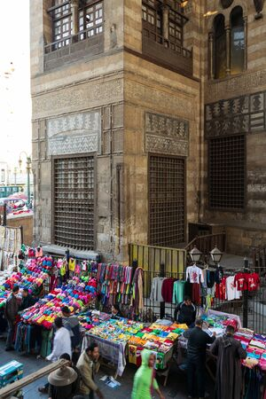 Cairo, Egypt- January 16 2016: Stalls with colorful clothes located outside old shabby Sultan al Ghuri Mausoleum building on Moez street Stock Photo - 133074418