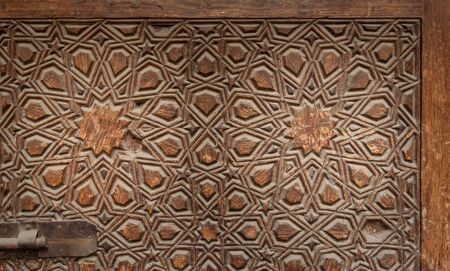 Geometrical engraved decorations of an aged wooden ornate door leaf, Old Cairo, Egypt Stock Photo - 131870207