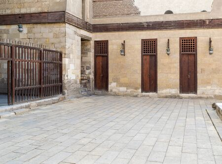 Three adjacent doors in a stone bricks wall and wooden fence at the main courtyard of public historic mosque of Sultan Al Nassir Qalawun, Cairo, Egypt Stock Photo - 131870463