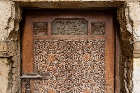 Geometrical engraved decorations of an aged wooden ornate door of Abd El Latif El Korafi historic mosque, signed by the maker, Gamalia district, Old Cairo, Egypt Stock Photo - 131871057