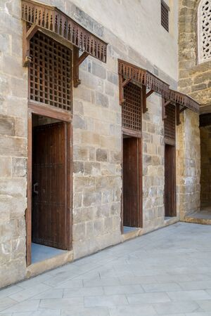 Facade of old abandoned stone bricks wall with three open weathered wooden doors and windows covered with wooden grid, Old Cairo, Egypt Stock Photo - 131870523