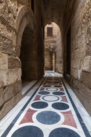 Vaulted passage leading to the Courtyard of Sultan Qalawun mosque with geometrical pattern colorful marble floor, Moez Street, Old Cairo, Egypt Stock Photo - 131871103