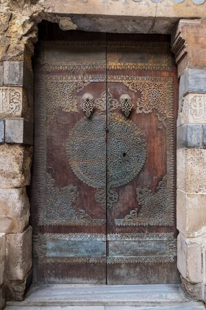 Wooden decorated copper plated door leading to Sultan Barquq mosque, Al-Moez Street, Old Cairo, Egypt Stock Photo - 131870560