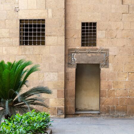 Ancient external old decorated bricks stone wall with two windows and opened door leading to Ottoman era Beit El Sehemy historical building, Cairo, Egypt Stock Photo - 131870679