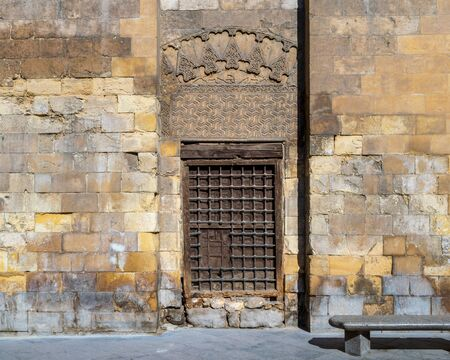 Grunge wooden window with decorated iron grid over stone bricks wall and marble garden bench, Moez Street, Cairo, Egypt Stock Photo - 131870411